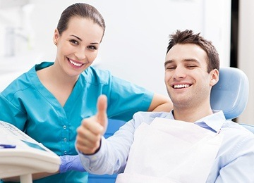 Smiling dental assistant and man in dental chair