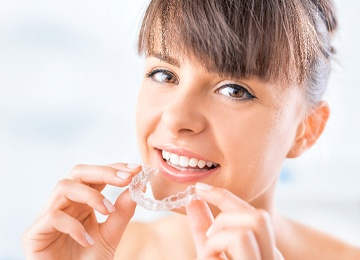 Woman using Invisalign clear aligner