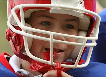 Child placing sports mouthguard
