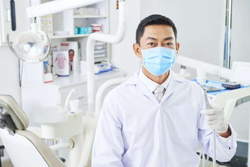 a dentist in Stuart wearing a lab coat and face mask while holding a dental instrument
